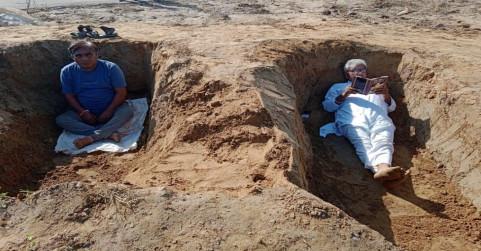 किसानों का नए अंदाज में किया विरोध, मांगें पूरी नहीं होने पर कब्र में लेटकर पढ़ी किताब